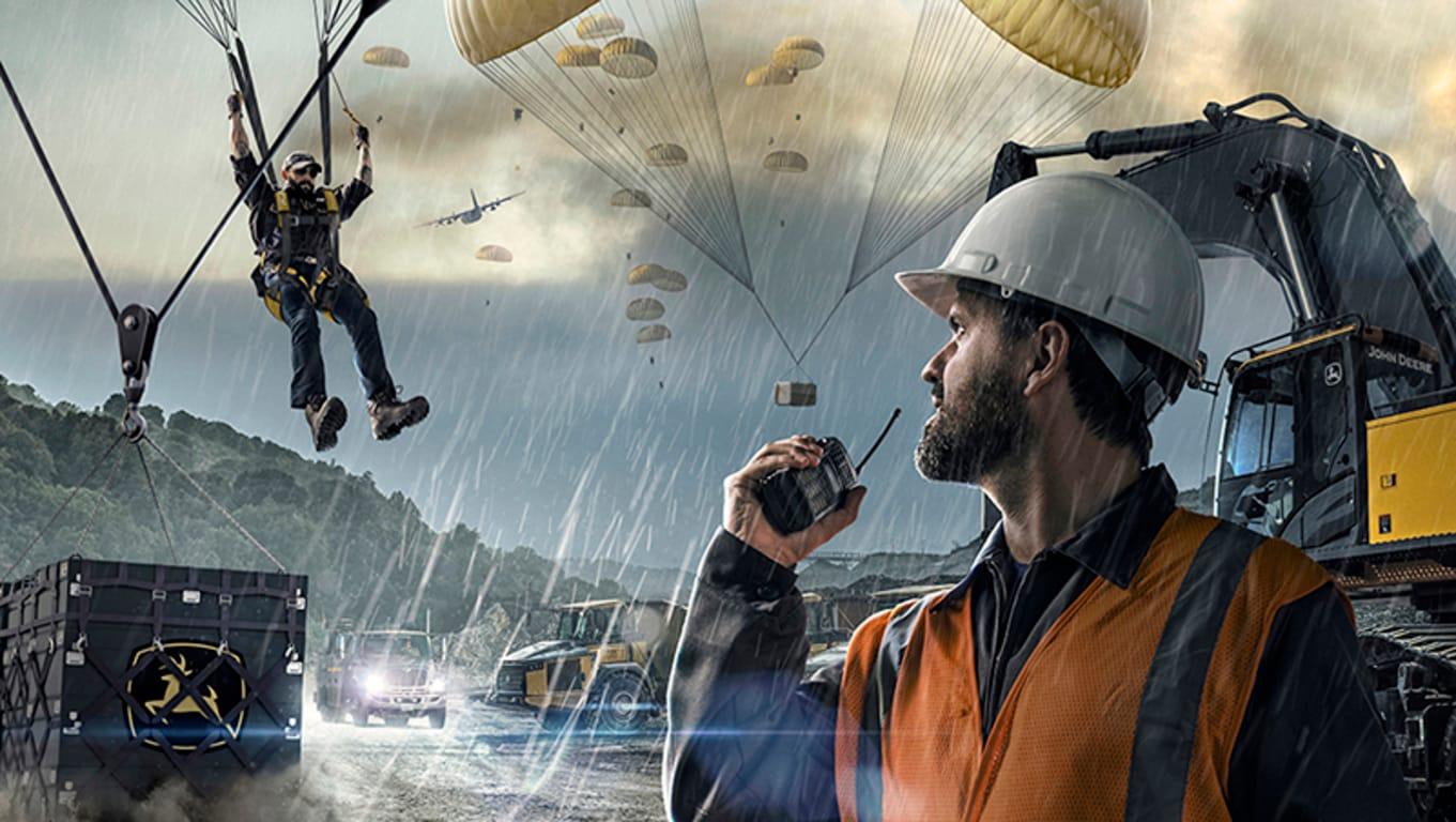 Personal de soporte del concesionario Deere que llega en paracaídas a un lugar de trabajo ficticio con cajas de envío de piezas.